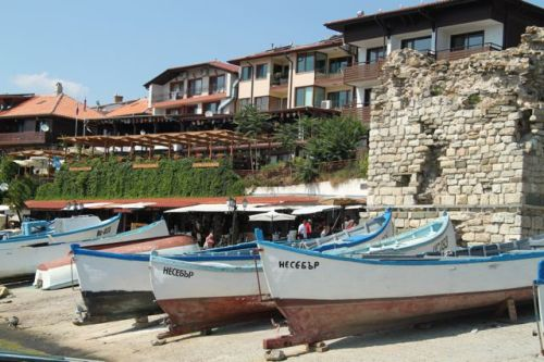 Colourful boats on the beach and a crumbling wall look authentically traditional.