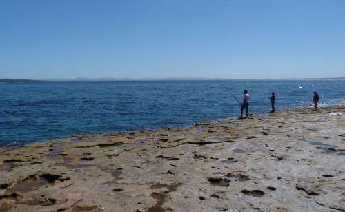 Fishing off the rock ledge.