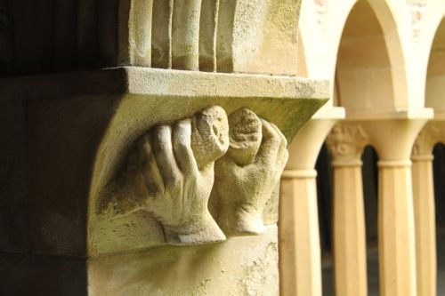 Detail from the cloister. Whose hands are they and what are they holding?
