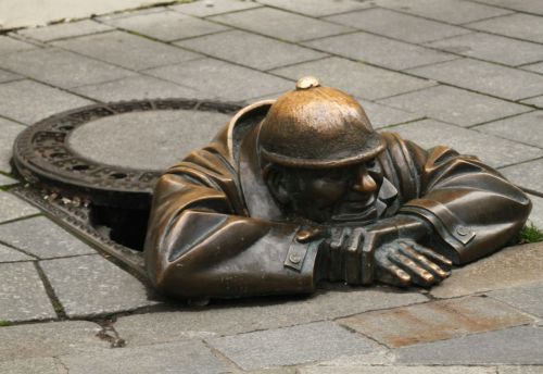 Cumil, the watcher, emerges from a manhole...