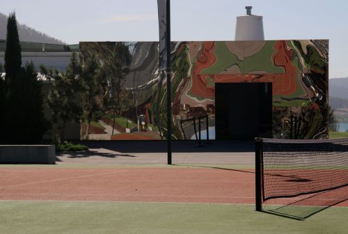 I don't understand the significance of the full size tennis court outside the entrance - though it's obvious that a lot of winners hit to the south would result in lost balls. Does this say something about the futile cost of human athletic endeavour?
