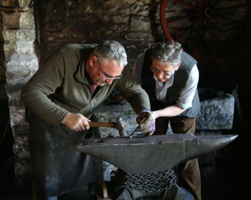 Blacksmiths taking a lot of care making a decorative ram's head fire poker.